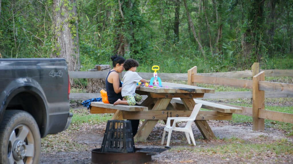 Mother and daughter play at a picnic table at Bayside Campground.