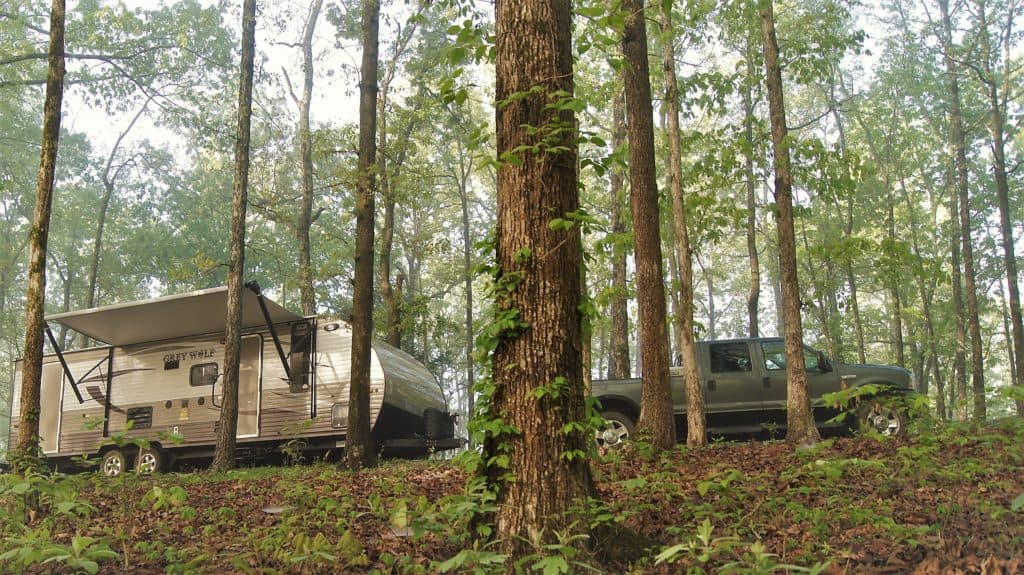 A travel trailer and truck are parked in the Tennessee woods in Meriwether Lewis Monument Campground.