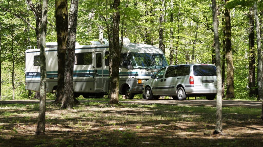 A motorhome and van are parked at a campsite in the Meriwether Lewis Monument Campground
