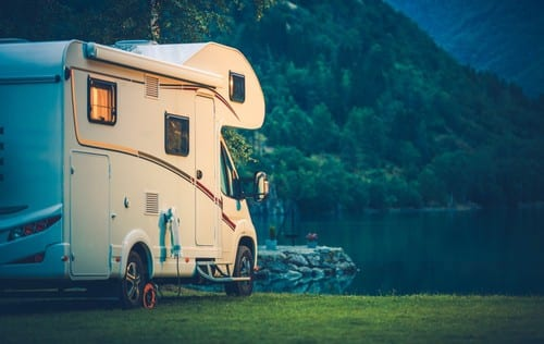 Motorhome parked by a lake.