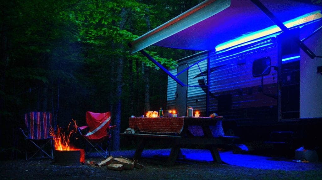 A travel trailer at night light up by a campfire, candles and blue LED lights