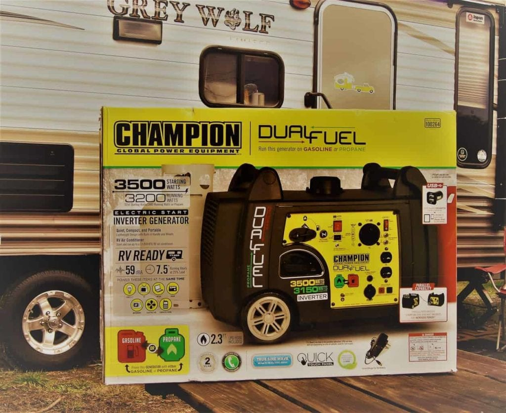 A Champion generator in a box in front of a Grey Wolf travel trailer
