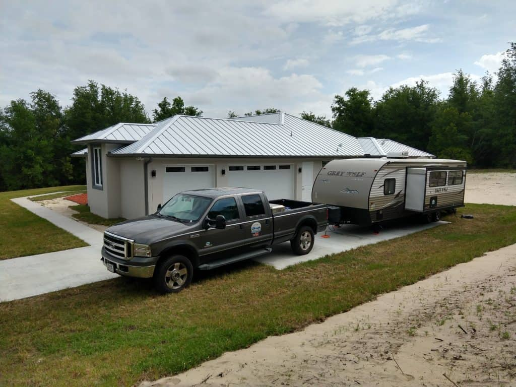 A truck and trailer parked in a driveway.