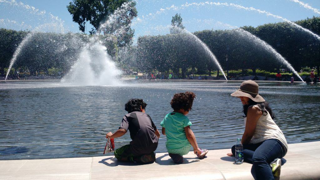 A mother sits on the edge of a large fountain with her two children.