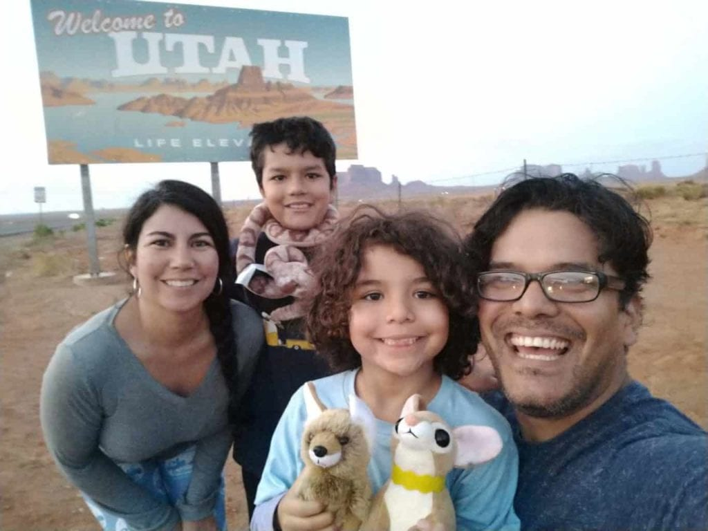 A family of 4 poses in front of the Utah welcome sign.