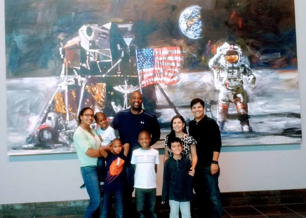 Two Roadschooling families pose in front of lunar landing painting.