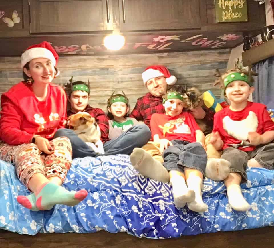 A family of 6 posing in Christmas gear