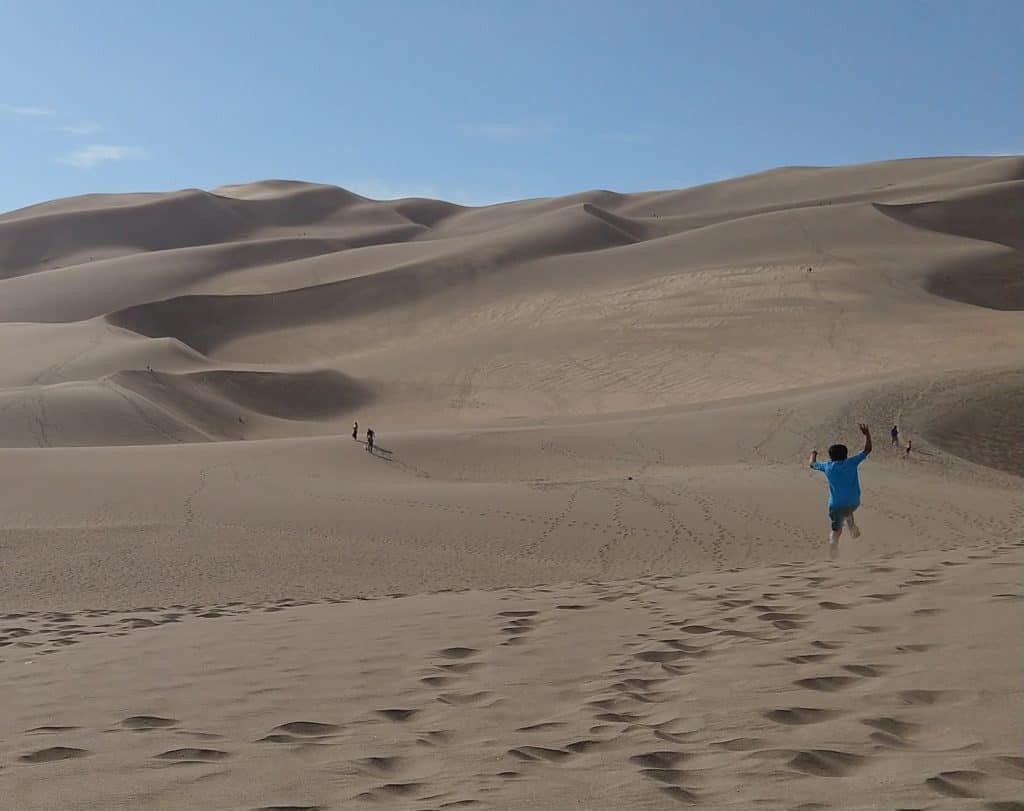 A boy leaps into the air on one of the dunes at the Great Sand Dunes National Park and Preserve.