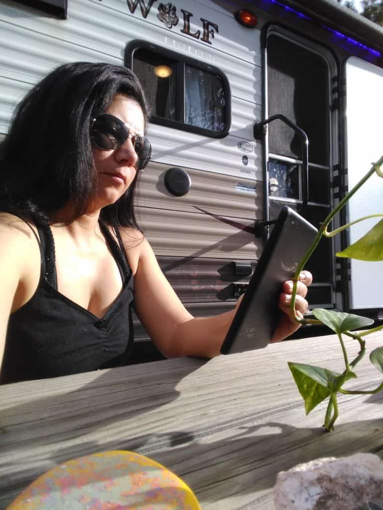 A woman reads her kindle at a picnic table