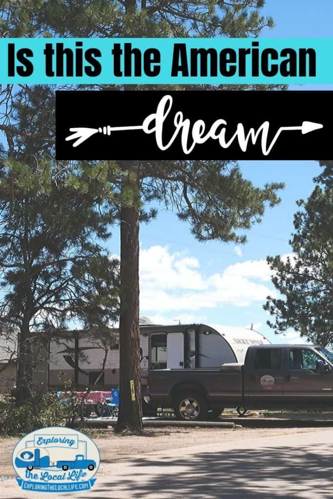 A truck and trailer are parked amongst pine trees and open skies.
