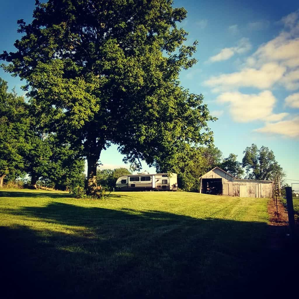 RV parked under trees and near a barn.
