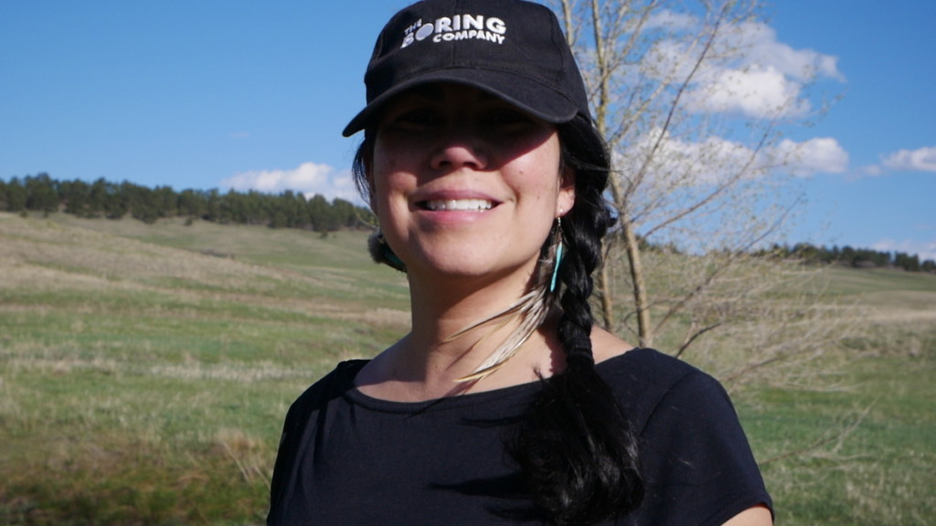 A woman poses while on a hike